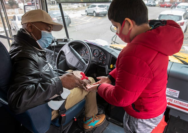 Jefferson County Public Schools demonstrate how the return to in-person learning will be handled in the pandemic. Bus driver Ronald Fawbush sprays sanitizer on the hands of Sayal Diswa outside of Gutermuth Elementary School. Feb. 22, 2021