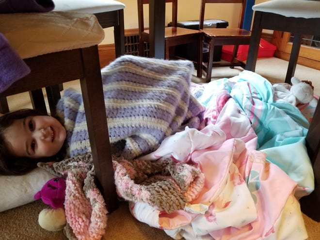 Amy Buck-Conrad's 3-year-old daughter, Lilah, sets up a fort under her mom's work-from-home space during the pandemic.