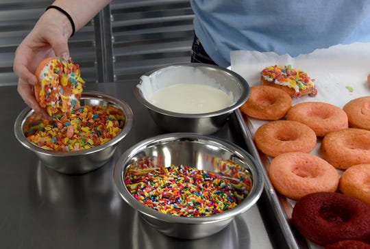 Josey Rutherford, owner of Simply Sweet Bakery in Newark, finishes doughnuts with white chocolate and either sprinkles or Fruity Pebbles.