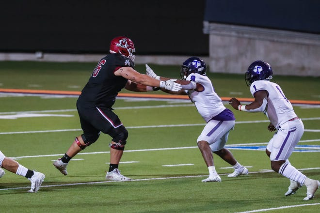 Sage Doxtater (76) blocks as the New Mexico State Aggies face off against the Tarleton State Texans at the Sun Bowl in El Paso on Sunday, Feb. 21, 2021.