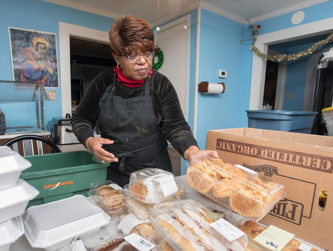 Sylvia Tisdale, the pastor of the Epps Christian Center, sorts donated food items at the Pace Blvd. center on Wednesday, December 19, 2018.