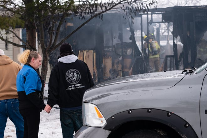 Family members of Jessica Webster watch as crews work to extinguish a fire in Webster's trailer in the 3800 block of Cherokee Drive in Burtchville Monday, Feb. 22, 2021.