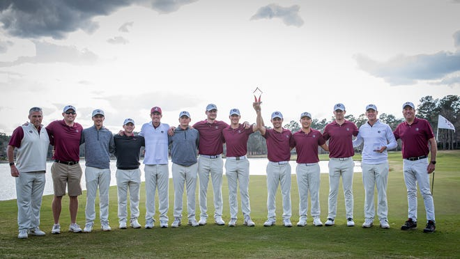 The FSU men's golf team raises the first-place trophy and celebrates its victory at The Seminole Intercollegiate at Gold Eagle Sunday.