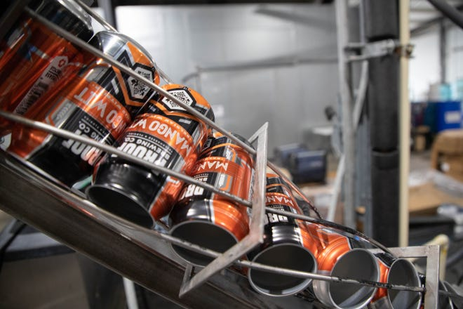 Cans of Proof Brewing Company's Mango Wit are filled at the brewery Monday, Feb. 22, 2021.
