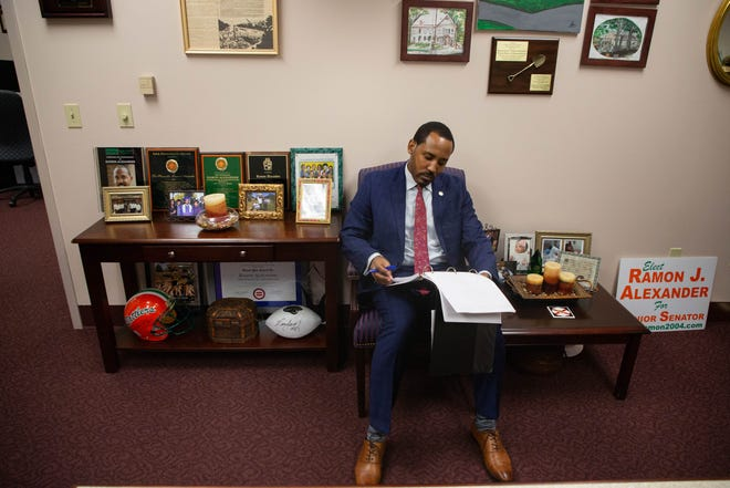 Rep. Ramon Alexander reviews materials from the Appropriations Committee in his office at the Capitol Monday, Feb. 22, 2021.