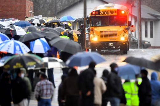 Members of the community gather in the rain at Austin-East High in Knoxville, Tenn. to escort and support students as they arrive to the school on Monday, Feb. 22, 2021. Austin-East students returned to in-person classes after the school went virtual for a week following the deaths of three students in three weeks.