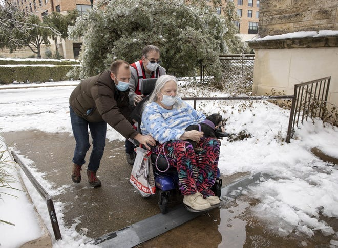 Dori Ann Upchurch is helped by Austin Disaster Relief Network volunteer Cody Sandquist, left, and a Red Cross volunteer to a warming station in Austin, after being evacuated from her home on Feb. 17.