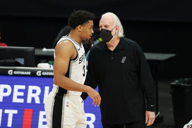 San Antonio Spurs coach Gregg Popovich, right, talks to Keldon Johnson during the team's game versus the Charlotte Hornets on Feb. 14. They will be without at least six players when they return to the court Wednesday at Oklahoma City.