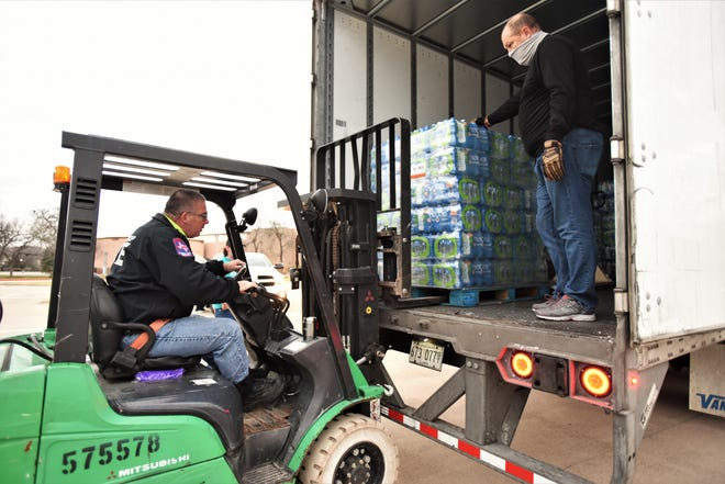 Bastrop firefighter Gilbert Demieville (left) and James Altgelt, Bastrop County assistant emergency management coordinator, unload on Sunday part of a shipment of 65,000 gallons of Niagara Bottling water delivered to Bastrop County under the State of Texas Assistance Request program.