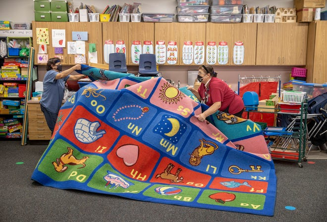 Custodians Raquel Zamudio, left, and Victoria Guerra try to dry out a wet rug Tuesday at Giddens Elementary School in the Leander school district. A frozen fire sprinkler line ruptured during the winter storm and flooded a significant portion of the school.