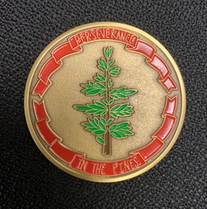 """As part of an art contest, students at high schools in Bastrop County  submitted designs for a commemorative coin marking the 10-year anniversary of the Bastrop County Complex Fire. One side of the coin features the phrase """"Perseverance In The Pines."""""""