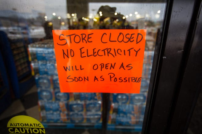 A sign states that a Fiesta Mart is closed because of a power outage in Austin on Feb. 17.