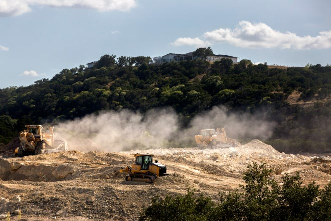 Bulldozers level ground to build homes in the Sweetwater community off Highway 71 in Bee Cave in 2019.  As more people move to the Hill Country, the demand for products from quarries, including limestone and other aggregates, has increased dramatically. [BRONTE WITTPENN/AMERICAN-STATESMAN]