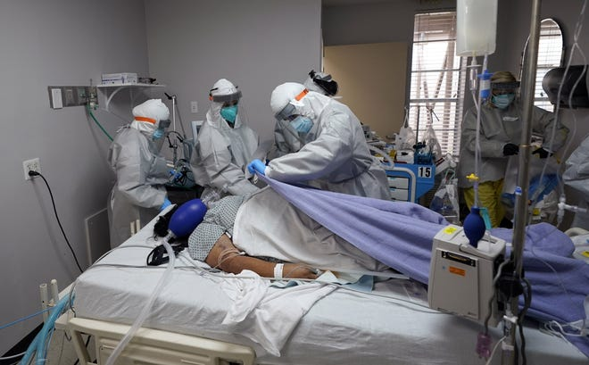 A blanket is pulled to cover the body of a patient after medical personnel were unable to to save her life inside the coronavirus unit at United Memorial Medical Center in Houston on July 6, 2020. [AP Photo/David J. Phillip, File]
