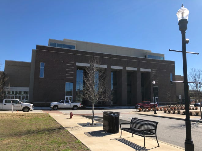 Workers' trucks stand parked Tuesday outside the Columbia County Performing Arts Center in Evans. Crews mostly are concentrating on interior work to complete the facility during the spring.