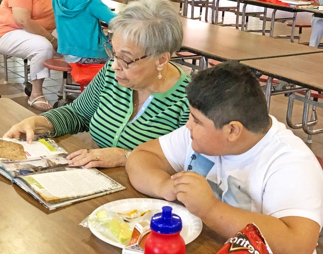 Even after she left the classroom to work in the district office, Jaci Bearden (left) often volunteered to be a reading buddy with students. She's pictured with student Juan Sandoval (right) in this undated photo. [Contributed Photo]
