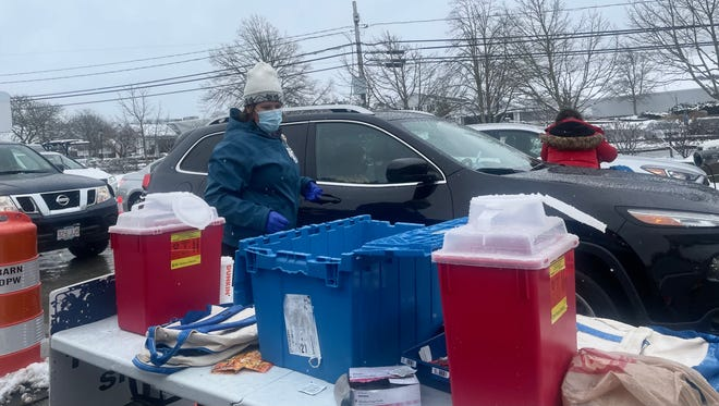 Valerie Al-Hachem, director of the Infectious Disease Dept. at Cape Cod Healthcare, and her colleagues administer vaccines in the sleet last week at the Cape Cod Melody Tent drive-thru site.