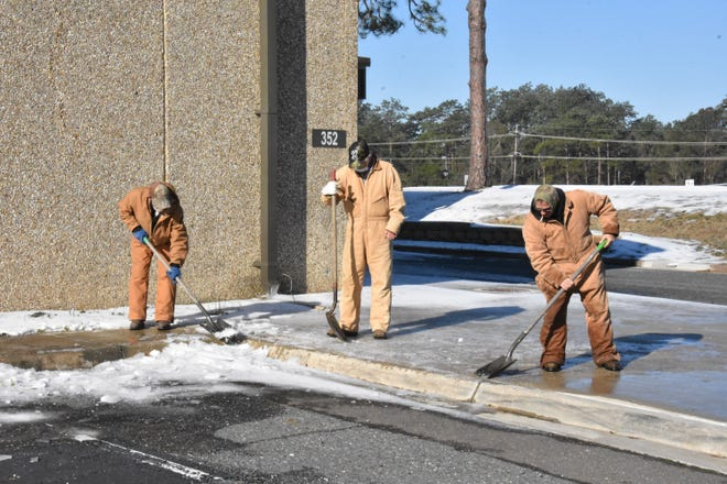Maintenance employees clear hazardous ice on sidewalks in front of Fort Polk facilities as the sun appears today and temperatures begin to warm.
