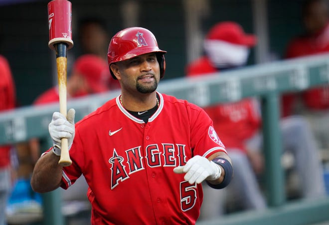 Los Angeles Angels' Albert Pujols waves to players in the Colorado Rockies dugout during a game Sept. 12 in Denver. Pujols' wife apparently disclosed that the Angels slugger will retire after the upcoming season, though she later amended her social media post to be less definitive.