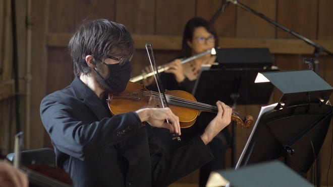 """Violinist Dominik Repka, left, and flutist Kimberlee Goodman play in the Everall Barn during the recording of the Westerville Symphony's performance of """"Appalachian Spring."""""""