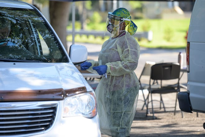 Health care workers conduct testing for COVID-19 at Lake-Sumter State College in Leesburg. [Cindy Peterson/Correspondent]