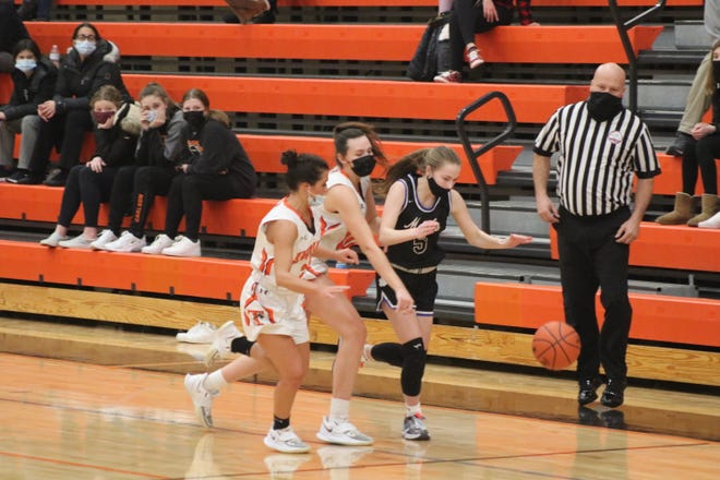 Tecumseh's Allie Barrett, left, and Jaden Benschoter, middle, knock the ball away from Adrian's Makenna Johnson (5) during the first quarter of Monday night's Southeastern Conference White Division game in Tecumseh.