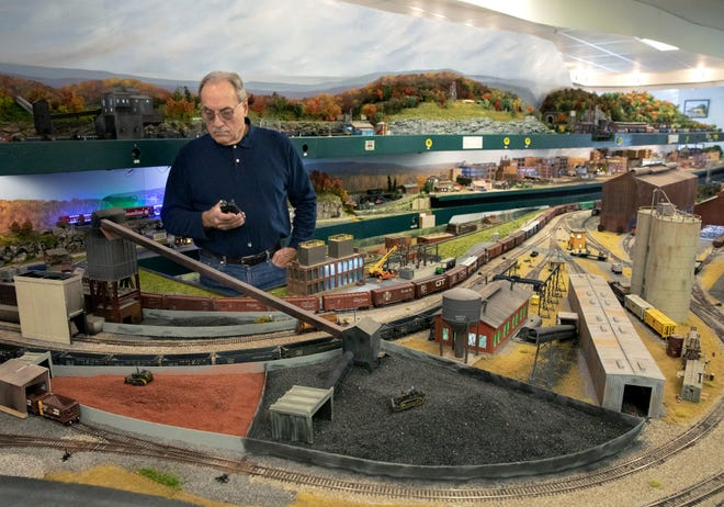 Blissfield Model Railroad club member Jerry Miklos, of Adrian, uses a remote control to direct a train during a December 2019 open house of the railroad club.