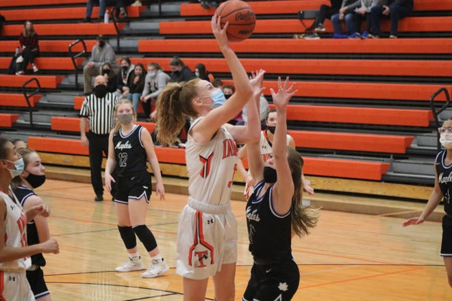 Tecumseh senior Hailey Dennes (3) shoots a layup over Adrian's Andra Patterson during the second quarter of Monday night's Southeastern Conference White Division game.