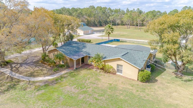 This five-acre fenced property in New Smyrna Beach includes a main home and an active dog and cat boarding and grooming kennel.