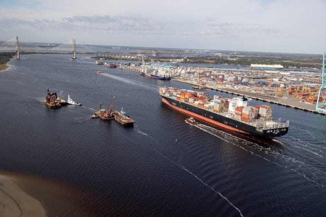 A container ship stacked with cargo approaches the Dames Point bridge.