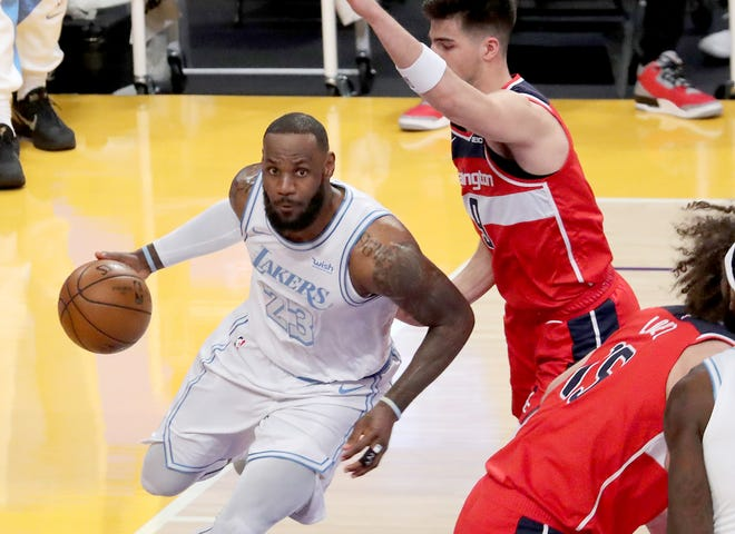 Lakers forward LeBron James drives to the basket againt Wizards forward Deni Avdija in the second quarter of Monday night's game at Staples Center on Feb. 22, 2021 in Los Angeles.
