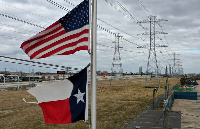 The U.S. and Texas flags fly in front of high voltage transmission towers on Feb. 21, 2021, in Houston, Texas. Millions of Texans lost power when winter storm Uri hit the state and knocked out coal, natural gas, and nuclear plants that were unprepared for the freezing temperatures brought on by the storm. Wind turbines that provide an estimated 24 percent of energy to the state became inoperable when they froze.