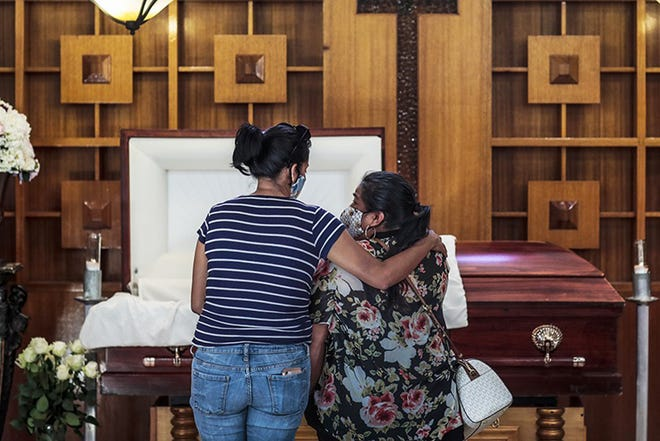 Iris Martinez weeps as she stands with another woman at the casket of her 60-year-old father, Rafael Martinez, after his death from COVID-19 in Los Angeles last summer.