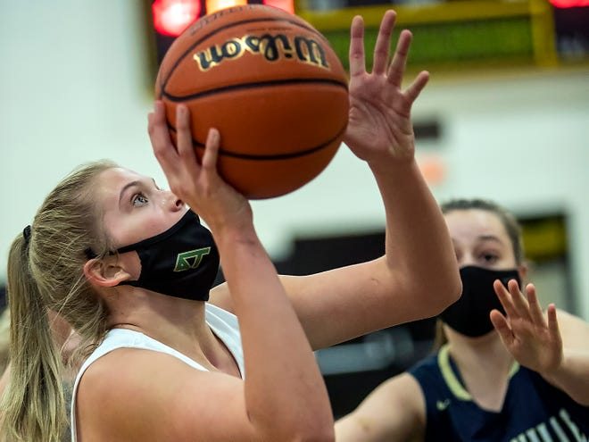 Abingdon-Avon junior Ashley Jones, left, eyes the basket as Knoxville's Ciara Shreeves defends during the Tornadoes' 59-39 win over the Blue Bullets on Monday night, in Abingdon.