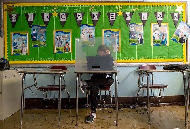 Churchill Junior High School seventh-grader Daniel Albert, 12, is socially distanced at the end of the classroom, as well as behind a plexiglass shield during Teresa Powell's English class on Tuesday, Feb. 23, 2021.