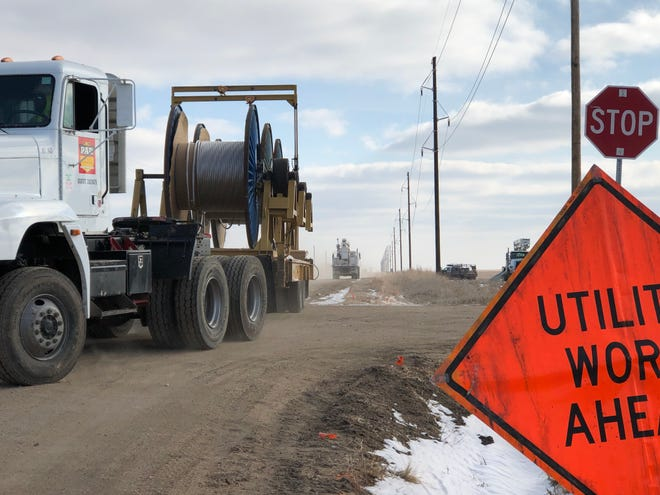 A crew member from Kansas City, Mo.,-based Par Electrical Contractors drives a truck hauling reels of conductor wire at Antonino and 270th roads last week as part of building a 16-mile 115-kilovolt transmission line installation southeast of Hays.