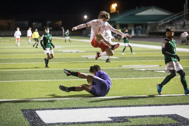 Levi  Hord (3) vaults East Henderson's goalkeeper, Aidan McAlister, as McAlister smothers the ball in the goal box during Monday's match at East.