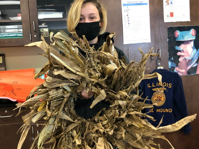 """Merisa Hill, a senior at Meridian High School, shows off the """"corn trash"""" wreath she made in horticulture class."""