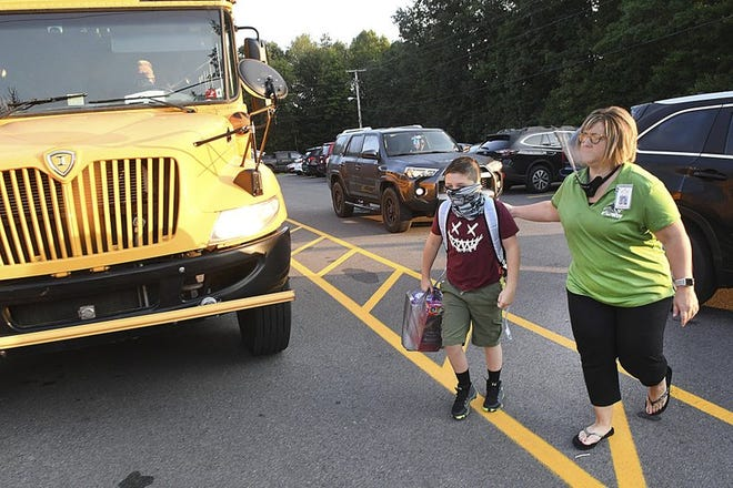 Hollywood Elementary School principal Tamber Hodges, right, walks Wyatt Hall to the school's entrance, in Mabsott, West Virginia, for the first day of school Tuesday morning, Sept. 8, 2020. As positive coronavirus cases continue to drop in West Virginia, the state school board says counties should return elementary and middle school students to in-class instruction five days per week. The board's vote Tuesday, Feb. 23, 2021 will eliminate blended schedules in which students have alternated between classroom and home-based online learning in response to the pandemic.