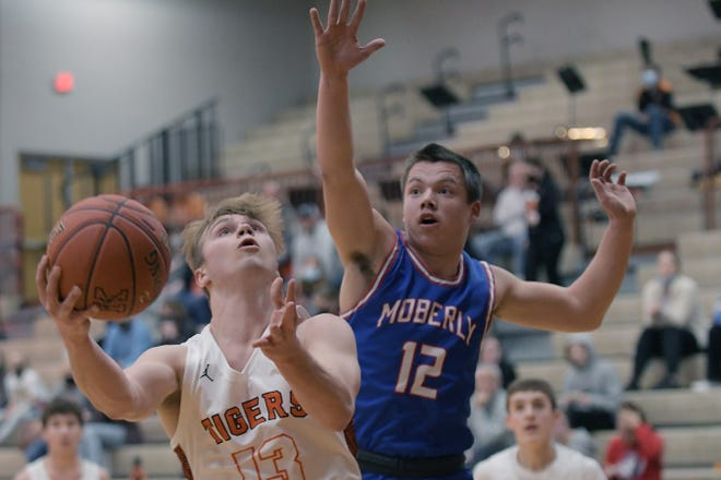 Moberly senior Dominic Stoneking (#12) reaches to contend a shot being released Monday by Kirksville's Noah Copeland. Stoneking scored seven points to help the Spartans hold off Kirksvillle winning 79-77.