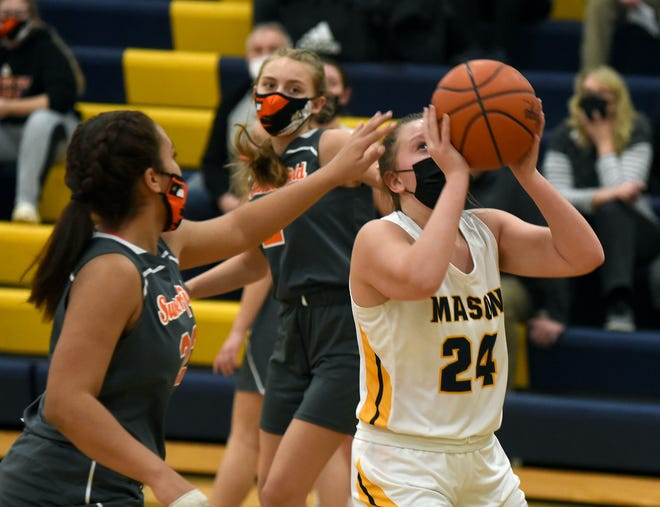 Ellie Trainor of Mason eyes the basket for a shot as Destanee Smith for Summerfield their to defend Monday night.
