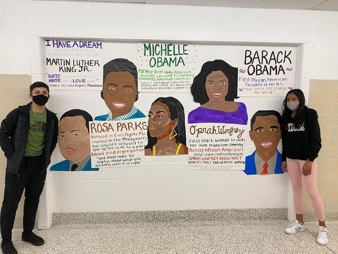 Bedford High School students Ilana Ravindra (right) and Hussein Jomaa stand in front of the display wall they created as part of the Black History Month program they spearheaded this February. The pair hope to continue to introduce diversity programs and celebrations at BHS in the coming months and years.