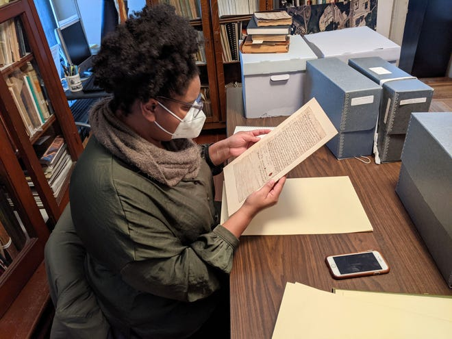 Mary McNeil, a Ph.D. candidate at Harvard University, examines documents at the Framingham History Center.