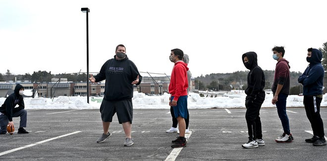 Valley Tech football coach Jim Archibald (second from left) speaks to his players during practice in the school parking lot on Feb. 23, 2021.