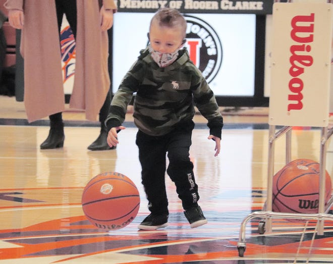 Hunter Fosdick chases a basketball tossed to him by his mother, Pontiac Township High School girls' basketball assistant coach Loren Fosdick, during halftime of Monday's game with St. Joseph-Ogden.