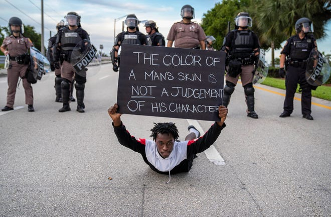 Demonstrator Davian Heller holds a sign in front of Florida Highway Patrol blocking Glades Road to prevent the marchers from going on to Interstate 95 while protesting the death of George Floyd in June of 2020 in Boca Raton.