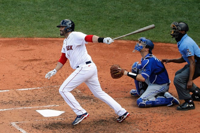 Red Sox designated hitter J.D. Martinez (left) follows through his swing on a hit against the Blue Jays during the third inning at Fenway Park last season.