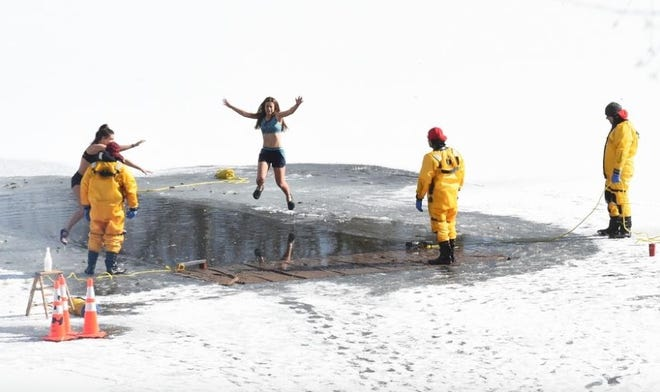 Emma Herman, center, jumps into the lake with her friend, Jenna Welch during the Polar Plunge at The Overlook in Kent in February 2019. The ninth annual Polar Plunge to benefit the Don Beckett Memorial Scholarship Fund is planned for Saturday from 10 a.m. to 1 p.m.