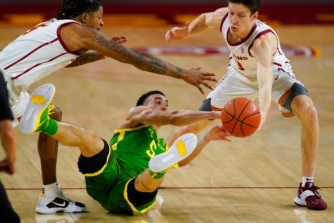 Southern California guard Isaiah White, left, guard Drew Peterson, right, and Oregon guard Chris Duarte (5) reach for a loose ball during the second half Monday. (AP Photo/Ashley Landis)