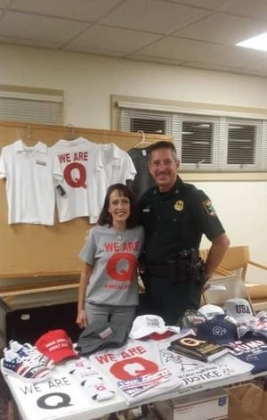 Then Sarasota County Sheriff's Office Col. Kurt Hoffman poses for a photograph at a merchandise table early last year. Hoffman, now sheriff, said he didn't know the woman was promoting a fringe conspiracy theory group known as QAnon.